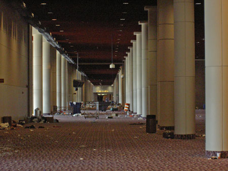 Building interior with large white columns and debris on red carpet