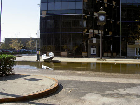Random boat washed up in front of commercial glass building