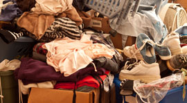 Residential hoarding scene with clothes and other items in big pile