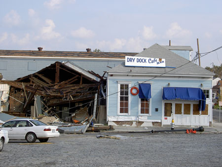 Dry Dock Café exterior with storm damage and exposed wood