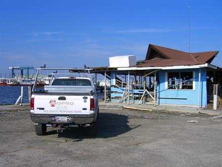 BIOPRO truck in front of warped  blue building following Hurricane Katrina