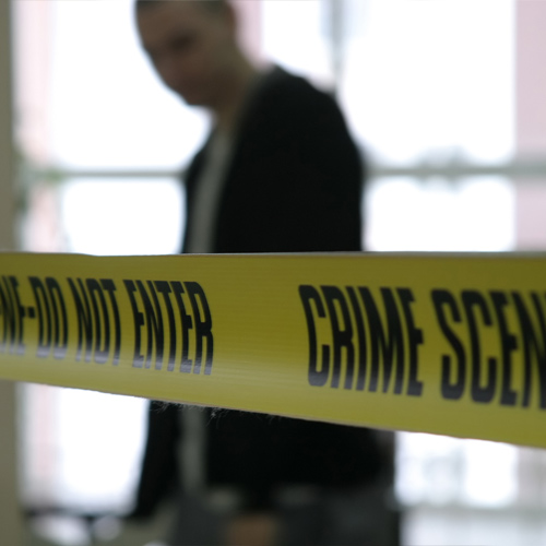 Man in black suit stands behind yellow crime scene tape